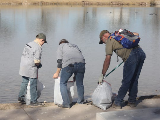 Volunteers from a local boy scout troop pick up trash