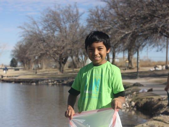 A.J. Prieto, 10, picks up trash along the Pecos River,