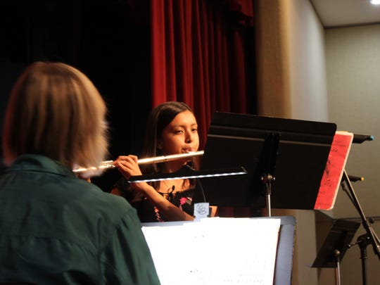 Yamalet Herrera performs a piece on the flute for the annual tea party and fundraiser.
