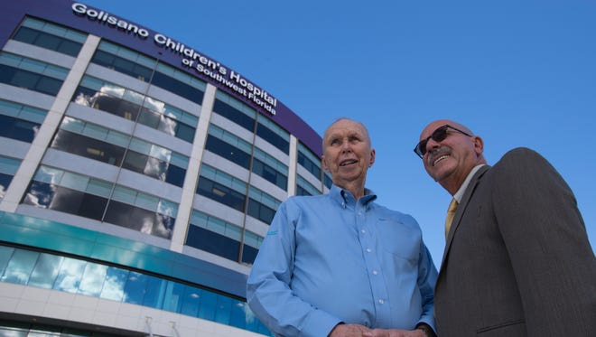 Al Kinkle, right, and Frank Haskell pose for a portrait in front of the Golisano Children's Hospital. Both men have lost daughters to different illnesses. They decided to turn their grief into keeping their daughters' memories alive by helping to raise millions of dollars to help youths and their families.