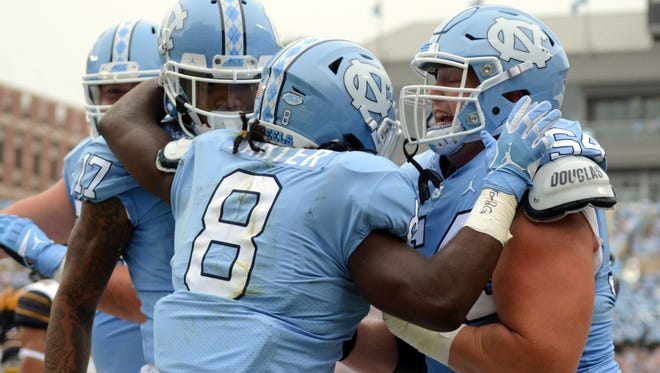 North Carolina Tar Heels running back Michael Carter (8) celebrates a touchdown with teammates during the first half against the California Golden Bears at Kenan Memorial Stadium.