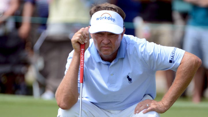 Davis Love III studies a putt on the 9th green during