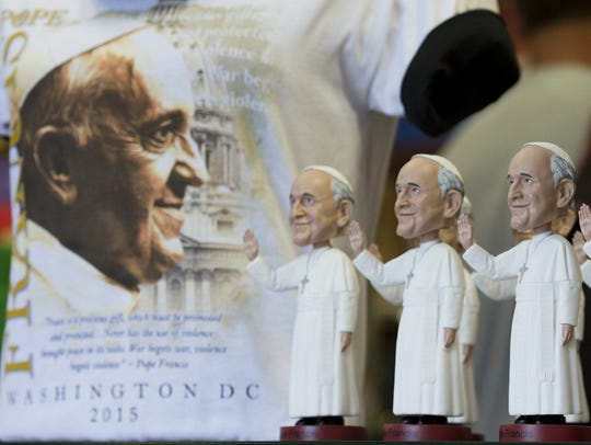 Pope Francis bobbleheads are displayed at a souvenir