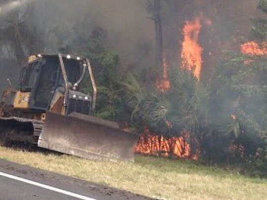 Crews try to put out the brush fire near Titusville