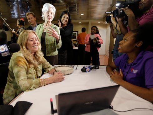 Department of Health and Human Services Secretary Kathleen Sebelius, center, talks with navigator Frantcia Thenor, right, and Carmen Celeiro, left, about health care options available under the Affordable Care Act at the North Shore Medical Center No