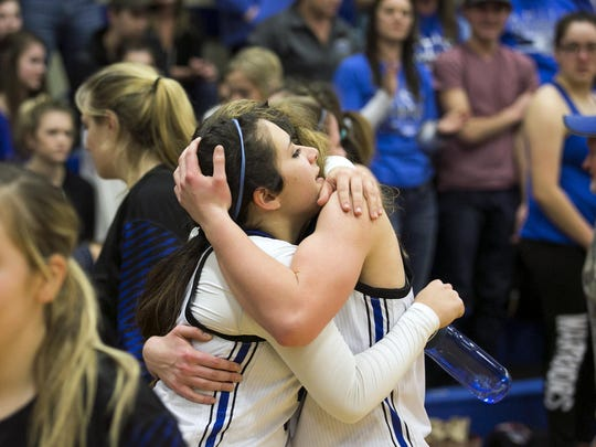 Amity players embrace after a close game in which they beat Dayton 46-42 at Amity High School on Friday, Jan. 29, 2016.