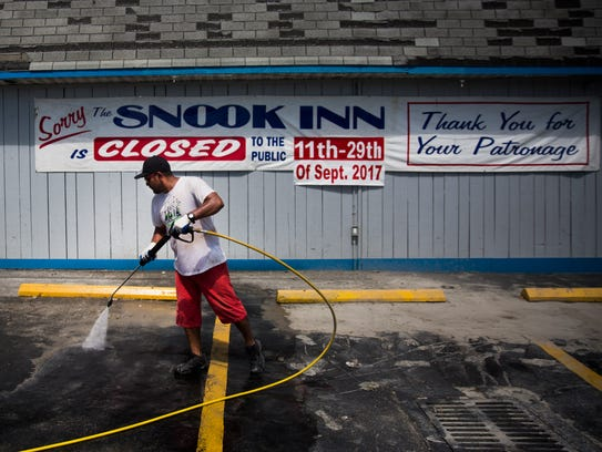 Roberto Valesquez pressure washes the parking lot at