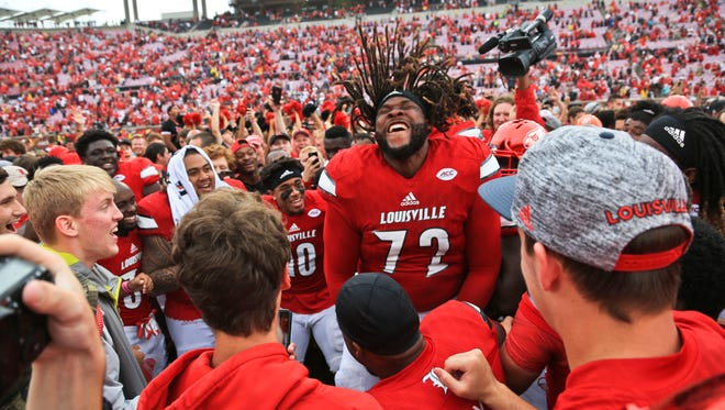 With hair flying, Louisville offensive lineman Lukayus McNeil jumps in the air with the crowd after the Cardinals routed the Seminoles 63-20 Saturday afternoon.
