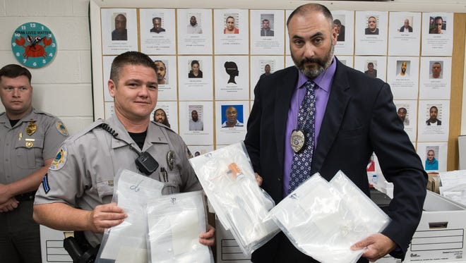 Private 1st Class Fontaine, left, and Detective Cpl. Brian Whitman stand for a photo holding evidence from a recent drug bust involving 41 arrests at Crisfield City Hall on Thursday, May 11, 2017.