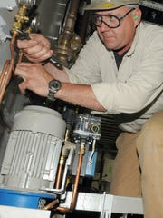 Pipefitter Marc Mraz of Forestville adjusts instrumentation