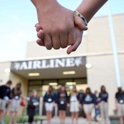 Students and supporters pray outside Airline High School