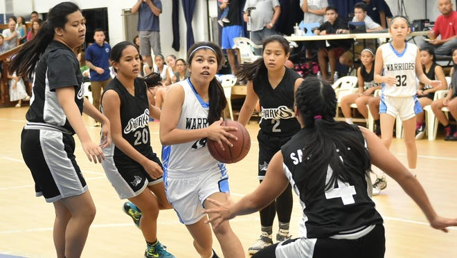 St. Paul Warriors' Joy Pangelinan drives through four Simon Sanchez Shark defenders in an Independent Interscholastic Athletic Association of Guam Girls' Basketball League game at St. Paul on Nov. 27. Pangelinan would pull up and hit a 10-foot floater, en route to being the game's high scorer.