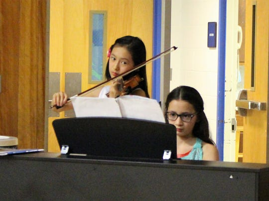 "Mt. Horeb fifth-graders May Yie (left) and Ava Maloney perform a violin/piano duet as part of a ""Genius Hour"" presentation to Board of Education members at the April 24 meeting."