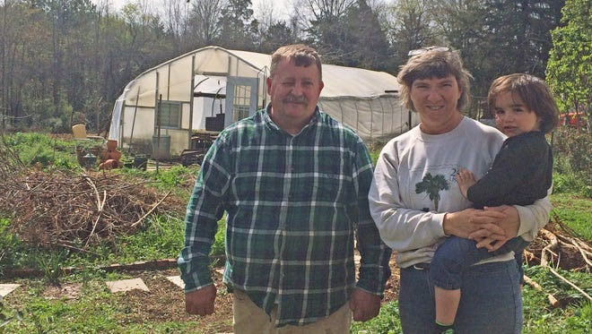 Rodger and Karen Winn with their grandson in the back yard of their Little Mountain home. Rodger has made a second career out of collecting heirloom vegetable and flower seeds.