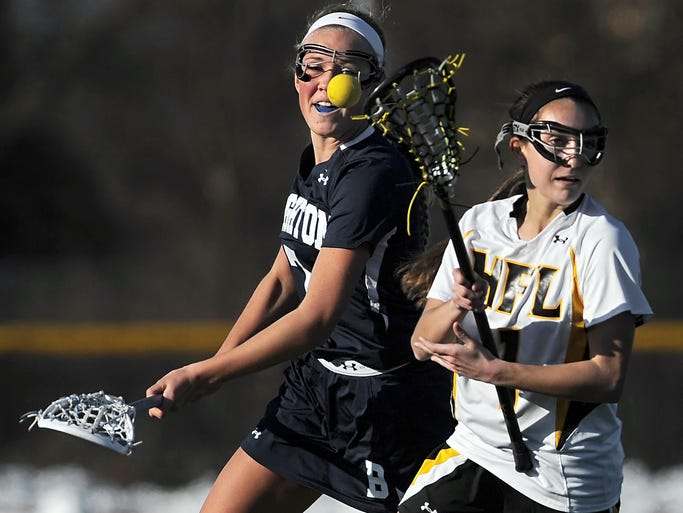 Brighton's Maggie McKenna, left, knocks the ball away from Honeoye Falls-Lima's Brittany Chamberlain during a regular season game played at Honeoye Falls-Lima High School on April 1, 2014.  Brighton beat HF-L 16-9.
