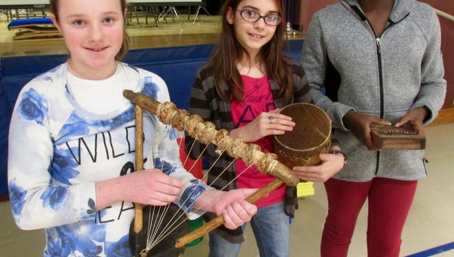 Rice Elementary School students (left to right) Morgan Guers, Juliana Donato, Tamia Crawford hold instruments from Africa they were given recently. Students at the school collected pencils for students in Africa.