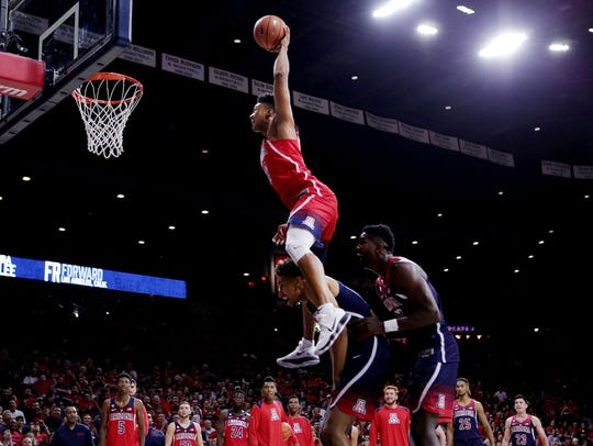 Arizona Wildcats forward Ira Lee (11) soars over teammates