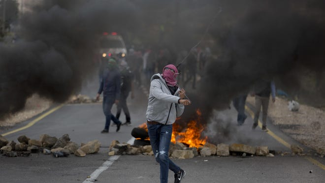 A Palestinian protester uses a slingshot during clashes with Israeli troops following protests against President Donald Trump's decision to recognize Jerusalem as the capital of Israel, at the outskirts of the West Bank city of Bir Zeit on Tuesday