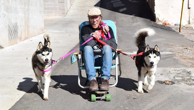 Georgie Cutright and his two Siberian Huskies, Sarah and Lobos, speed down a hill behind Cumberland Avenue in Knoxville on Wednesday, Feb. 15. Cutright says he will attempt to travel from Knoxville to California, a more than 2,000-mile haul.