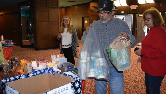 Justo Lopez of Vineland donates toiletries to the Christmas for Puerto Rico collection drive that was held Saturday at Landis Theater in Vineland.