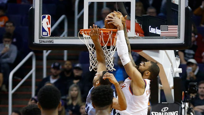 Phoenix Suns center Tyson Chandler, right, dunks the winning shot against Memphis Grizzlies forward Brandan Wright, back left, during the second half of an NBA basketball game, Tuesday, Dec. 26, 2017, in Phoenix. The Suns defeated the Grizzlies 99-97.
