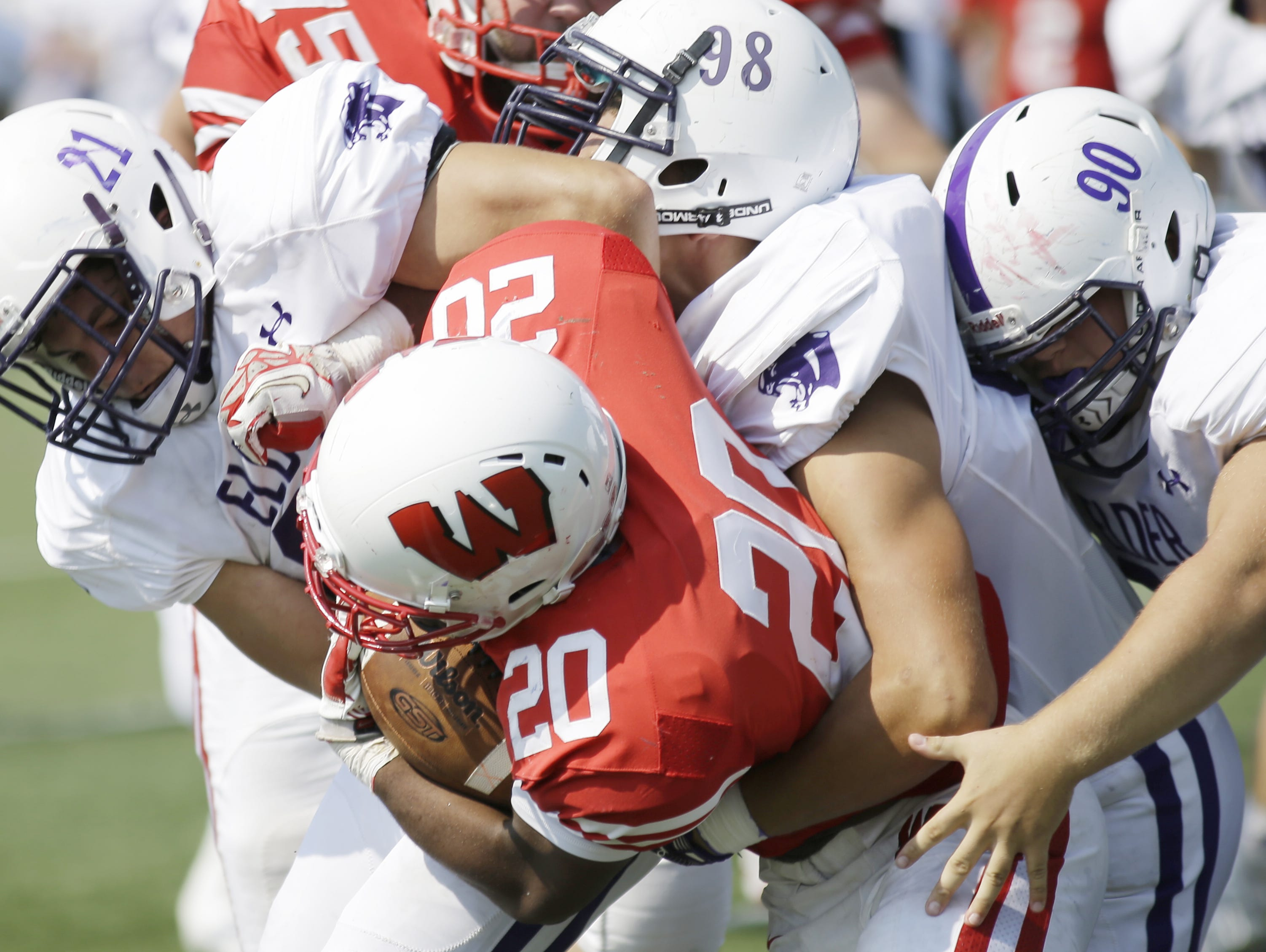 Lakota West running back Danny Otakasongo is wrapped up by several Elder defenders during the Firebirds' 34-17 loss on Saturday.
