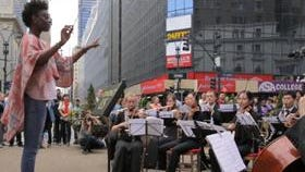 Random passersby turn into orchestra  conductors at a Manhattan plaza.