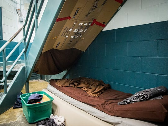 An inmate positioned on a cot in a cell block due to overcrowding uses cardboard to block light in the common area at the Delaware County Jail Wednesday.