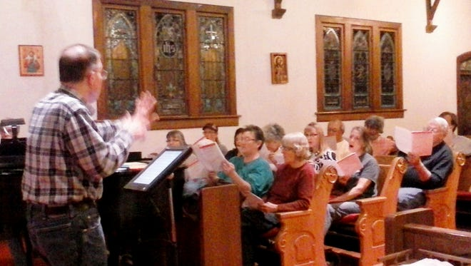 Community Chamber Singers director Mick Coon leads the choir in practice on April 11.