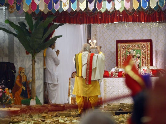 A temple priests performs a ceremony during the house