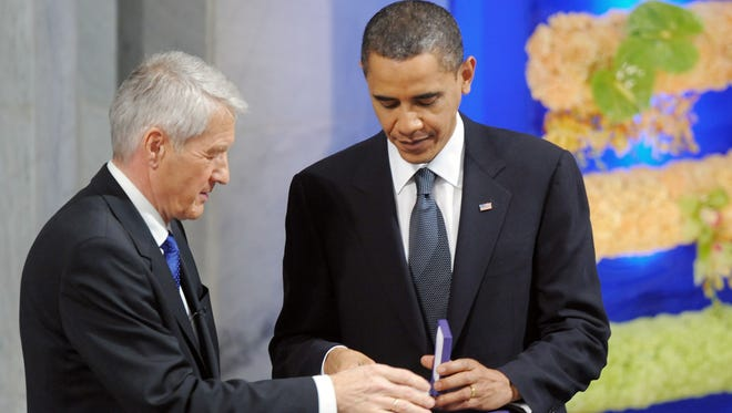 Norwegian Nobel Peace Prize Committee chairman Thorbjoern Jagland hands the 2009 Nobel Peace Prize to President Obama during a ceremony in Norway.