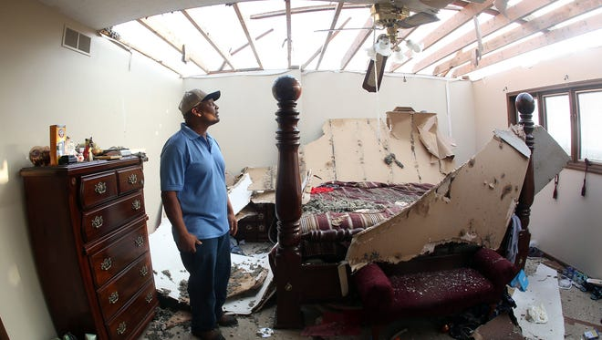 Virgil Toombs 2621 Jeep Rd., Abilene, Kan., looks over his bedroom Thursday, May 26, 2016, after Wednesday nights tornado ripped part of the roof off. (Thad Allton/The Topeka Capital-Journal via AP)