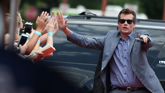 """John Green gives high fives as he arrives at the red carpet during the """"Paper Towns"""" movie tour at Old National Centre, Tuesday, July 14, 2015."""
