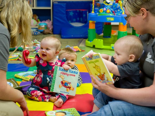 Vectren volunteers for the United Way Day of Caring Jennifer Buckman (left) and LeAnna King spend their hours reading and entertaining infants at The Arc of Evansville Friday morning. The kids are (from left) Emmaline Gilbert, Louis Langerak and Max Clem.
