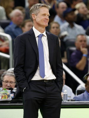 Golden State Warriors head coach Steve Kerr smiles as he looks on against the Orlando Magic during the first quarter at Amway Center.