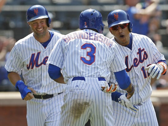 Michal Cuddyer, left and Curtis Granderson celebrate after scoring on Lagares's sixth-inning, three-run home run in Sunday's game.