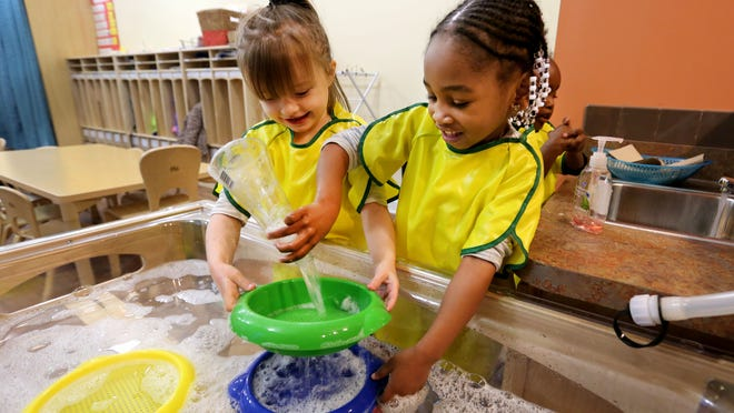Karley Clayton, 4, left, and Shaniaya Wright, 3, play at the sensory table at the new Robert & Adele Schiff Learning Center II in Lower Price Hill in December.
