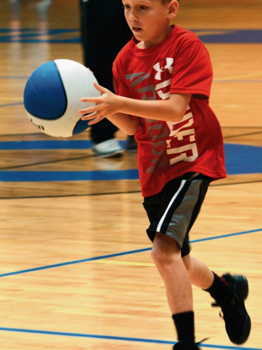 Matt Hollinshead — Current-Argus Wyatt Widener, 9, drives toward the basket during buzzer-beater drills Wednesday at the fourth-annual Cavemen basketball camp.