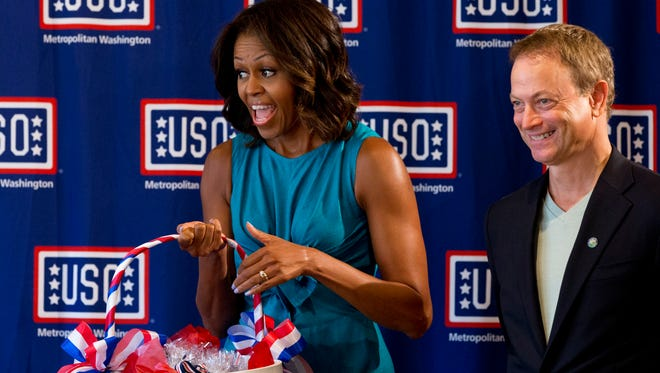 First lady Michelle Obama, with actor Gary Sinise, visit USO Warrior and Family Center at Fort Belvoir, Va., toting basket of dog-shaped cookies, on 12th anniversary of Sept. 11 attacks.
