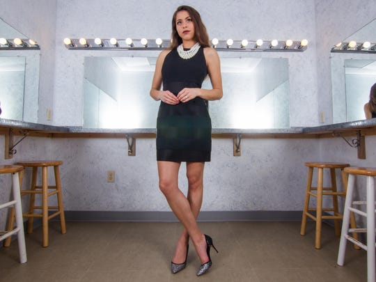 Selena Barnett wears a high neck black dress with black silk stripe detailing; pearl  earrings and necklace; silver and black Swarovski crystal heels.