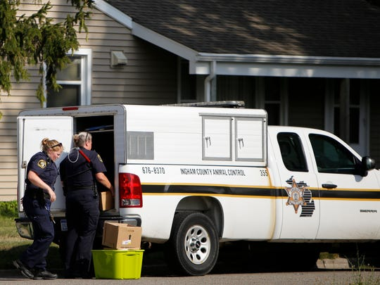 Ingham County Animal Control officers take away boxes