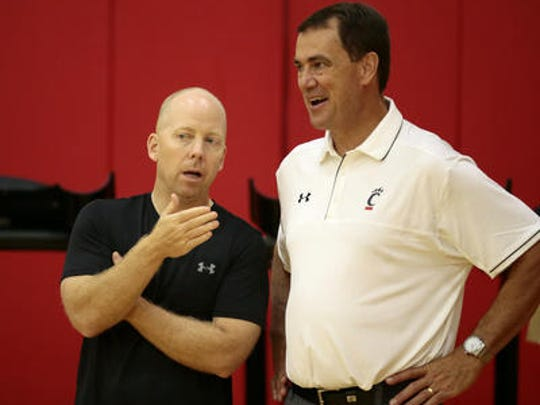 UC men's basketball coach Mick Cronin (left), here with Bearcats athletic director Mike Bohn at a recent practice, said his focus is on his team and not realignment talk.