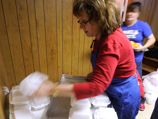 Connie Decker unloads a tray of desserts for to-go orders during St. John's United Methodist Church's annual Christmas dinner in 2014.