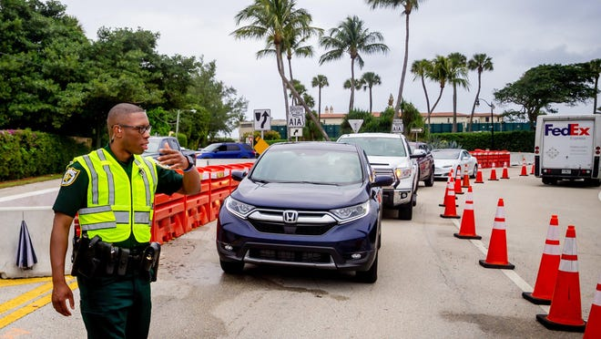 A Palm Beach County Sheriff's deputy directs traffic outside of Mar-a-Lago in December. Traffic restrictions will start Friday as President Trump is expected back in town this weekend.