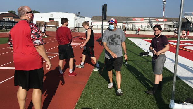Fort Osage offensive line coach Rick Ammons, left, visits with football head coach Brock Bult and players following an early-morning conditioning workout at the high school Tuesday. Fort Osage is allowing both indoor and outdoor conditioning and training sessions this week for freshman through senior student-athletes.