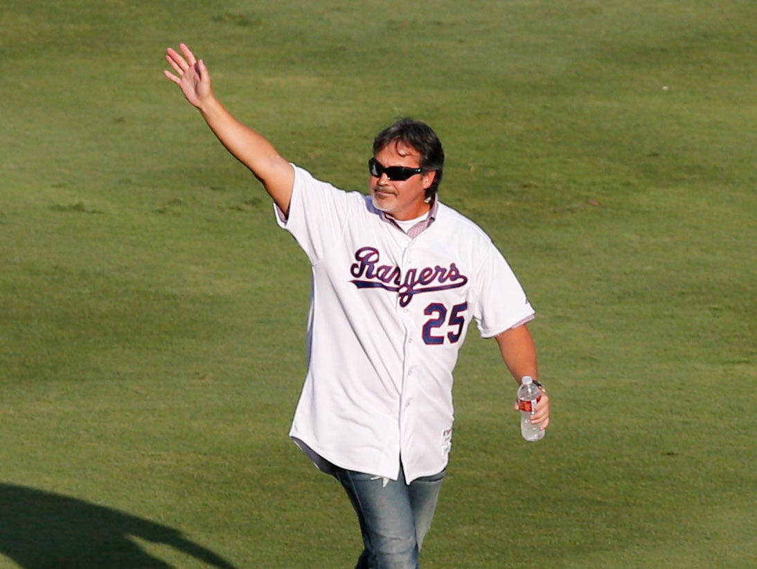 August 11, 2012; Arlington, TX, USA; Texas Rangers former player Rafael Palmeiro waves to fans during introductions of the Rangers 40th anniversary all time team before the game against the Detroit Tigers at Rangers Ballpark in Arlington. Mandatory Credit: Jim Cowsert-USA TODAY Sports