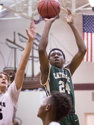 Crusader DJ McKenzie (24) shoots during the basketball game between Catholic and Navarre at Navarre High School on Tuesday, December 5, 2017.