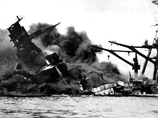 The battleship USS Arizona belches smoke as it topples