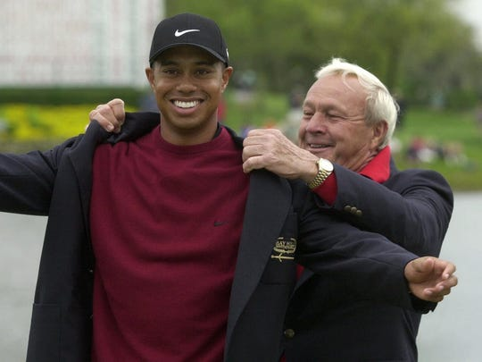 File-This March 18, 2001, file photo shows Tiger Woods, left, being helped into his jacket for winning the Bay Hill Invitational by tournament host Arnold Palmer  in Orlando.