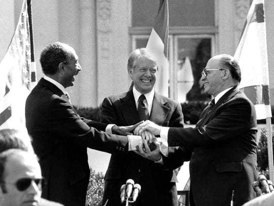 Egyptian President Anwar Sadat, left, U.S. President Jimmy Carter, center, and Israeli Prime Minister Menachem Begin clasp hands on the North Lawn of the White House after signing the peace treaty between Egypt and Israel on March 26, 1979. Sadat and Begin were awarded the Nobel Peace Prize for accomplishing peace negotiations in 1978.